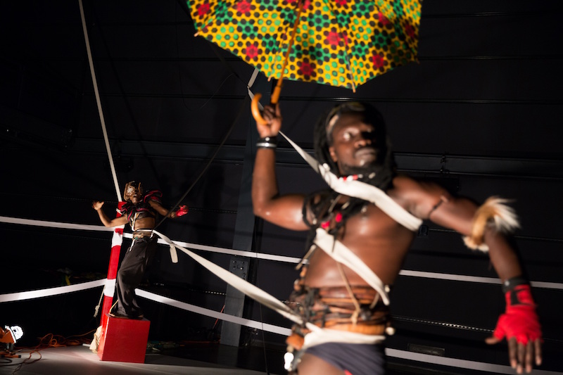 A close up of a shirtless black in a box ring. Harnesses and ropes entangle his torso.