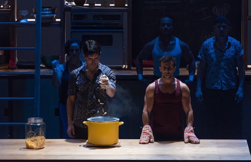 A group of performers watch a man throw pasta in a yellow pot