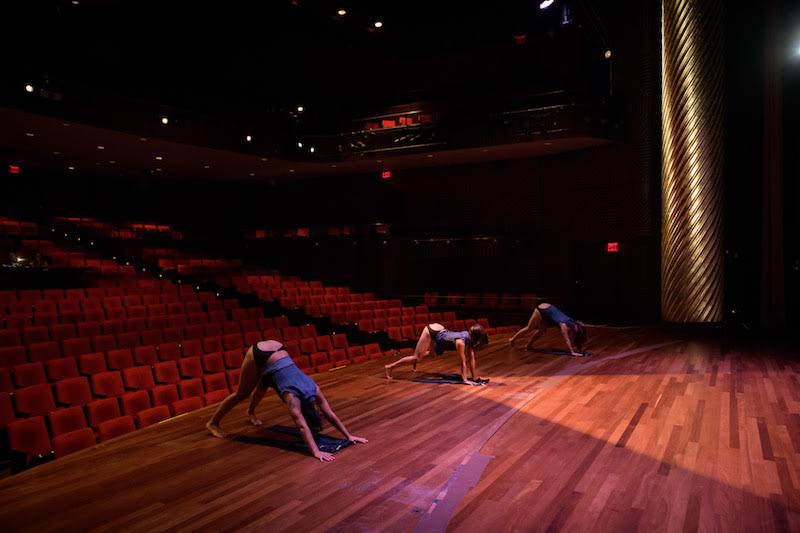 Three women crouch with their hands and feet on the ground while their haunches face out to the auditorium.