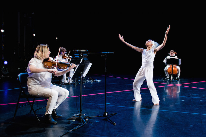 McIntyre dressed in white reaching her arms overhead while the string trio sits in chairs around her