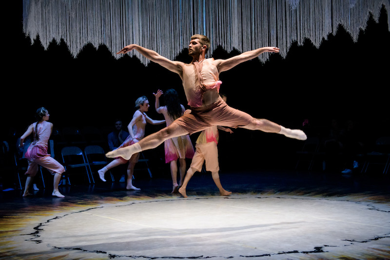 A male dancer in a pink hued gossamer costume leaps into the air. His legs extend perpendicular to the floor. Four other dancers move in the background.